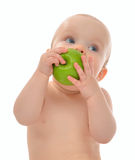 Infant child baby kid  eating green apple blue eyes looking at t Royalty Free Stock Images