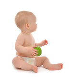 Infant child baby kid eating green apple blue eyes looking at th Royalty Free Stock Image