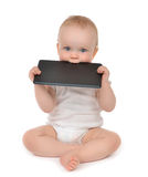 Infant child baby toddler eating digital tablet mobile computer. Infant child baby toddler sitting and eating digital tablet mobile computer isolated on a white Royalty Free Stock Image