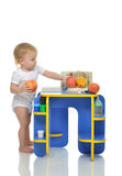 Infant child baby toddler kid happy standing and taking fruits p Stock Photos