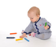 Infant child baby toddler sitting drawing painting with color pe. Ncils crayons on a white background Stock Photo