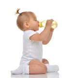 Infant child baby toddler sitting and drinking water from the fe Stock Images