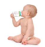 Infant child baby toddler sitting and drinking water. From the feeding bottle on a white background Stock Photos