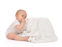Infant child baby toddler sitting and eating soft blanket towel Stock Photo