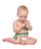 Infant child baby toddler sitting playing with tape measure meas Stock Image