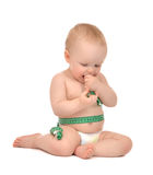 Infant child baby toddler sitting playing with tape measure meas Royalty Free Stock Images