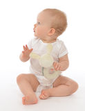 Infant child baby toddler sitting smiling with soft bunny toy. Looking at te corner on a white background Stock Photography