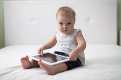 Infant child baby toddler sitting and typing digital tablet comp Royalty Free Stock Image