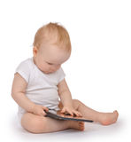 Infant child baby toddler sitting and typing digital tablet mobi Stock Photos