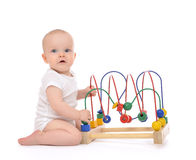 Infant child baby toddler standing and playing wooden educationa. L toy with looped wires for teaching coordination on a white background Stock Photography