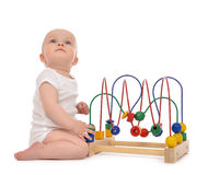Infant child baby toddler standing and playing wooden educationa Royalty Free Stock Images