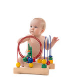Infant child baby toddler standing and playing wooden educationa Stock Image