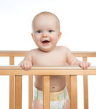 Infant child baby toddler in wooden bed looking up happy smiling. On white background Royalty Free Stock Photography