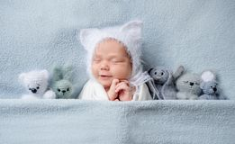 Infant child in bonnet with ears sleeping with toys. Adorable little infant child in cute bonnet with ears sleeping on the bed with small toys placed near him stock images