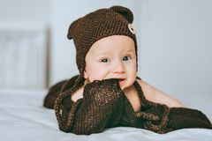 Infant child in brown knitted hat biting blanket. In bed royalty free stock photography