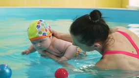 Infant Child Diving into the Paddling Pool. Close Up of Infant Child Diving into the Paddling Pool. Cute little Boy Learning to Swim with Swimming Instructor stock video