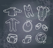 Infant clothes Icon set. Set of hand-drawn doodle icons baby clothes and accessories on a blackboard Stock Photo