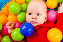 Infant with colorful balls royalty free stock photos