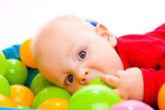 Infant with colorful balls Royalty Free Stock Image