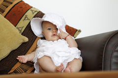 Infant on couch with hat Stock Photo