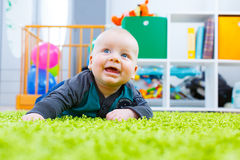 Infant crawling on the green carpet. In the child room Stock Images