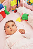 Infant in crib with toys Royalty Free Stock Photo