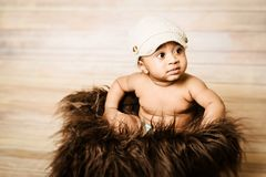 Infant dogla boy wearing hat sitting in a fluffy furry basket wooden background modern studio shoot Stock Image