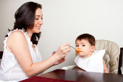 Infant eats messy. Beautiful happy mother or nanny feeds baby boy girl orange puree with spoon, infant eats messy, while sitting at table Royalty Free Stock Images
