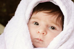 Infant face. Serious infant wrapped in white towel closeup face photo royalty free stock photos