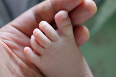 Infant feet. Close-up image of feet of an infant held by hands Royalty Free Stock Photo