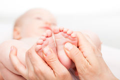 Infant foot massage. Close-up shot of three month baby girl receiving foot massage from a female massage therapist. Camera is focused on infant's feet. Face is royalty free stock image