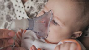 Infant getting breathing treatment from mother while suffering from illness. Face close up. Infant getting breathing treatment from mother while suffering from stock video footage
