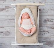 Infant girl asleep on a small crib. Infant girl in white asleep on a small crib Stock Photography