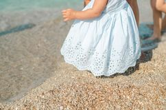 Infant girl in blue dress taking first steps in the sand with mom help at the sunny beach. Childhood and mother day concept royalty free stock photo