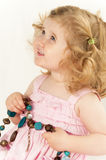 Infant girl holding a large bead necklace. Smiling baby girl,  nearly two years old, in a pink dress, looking up and holding a large bead necklace. Isolated on Stock Image