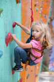 Infant girl making first steps on climbing wall Royalty Free Stock Photos