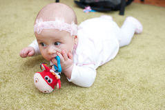 Infant girl in mother club play with toy. On the floor Royalty Free Stock Images