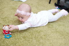 Infant girl in mother club play with toy. On the floor Stock Photos