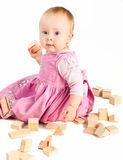 Infant girl playing with wooden blocks Royalty Free Stock Images