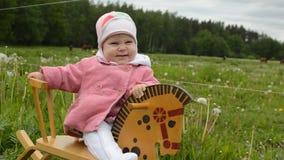 Infant girl rocking horse. Infant baby girl ridding rocking horse outdoor stock footage