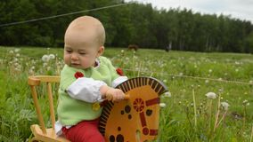 Infant girl rocking horse. Infant baby girl ridding rocking horse outdoor stock video footage