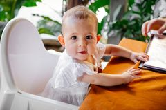 Infant girl is sitting on a baby high chair in a street cafe by the table. Children in white dress.  stock image