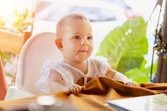Infant girl is sitting on a baby high chair in a street cafe by the table. Children in white dress dabbles and pulls the. Tablecloth stock photos