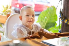 Infant girl is sitting on a baby high chair in a street cafe by the table. Children in white dress dabbles and pulls the. Tablecloth stock images
