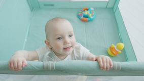Infant girl standing holding on to edge of playpen stock footage