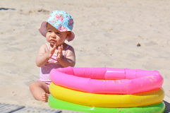 Infant girl with toy pool Stock Images