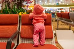Infant girl travels. First time at the airport. Baby in living coral hoodie standing on a chair, back to the camera.  royalty free stock photography
