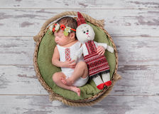Infant girl in Ukrainian costume sleeping with a toy hare Stock Images