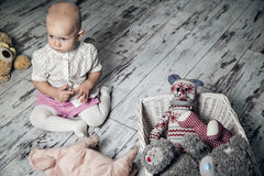 Infant girl upset alone with toys. On a wood flor at home Stock Photos
