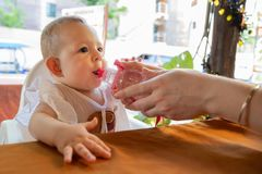 Infant girl in white dress sitting at the table on a high chair. Baby drink water from the bottle from mother hands on the street.  royalty free stock image